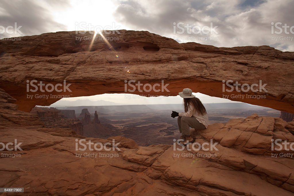 Hiker overlooks Mesa Arch Canyonlands National Park Utah stock photo