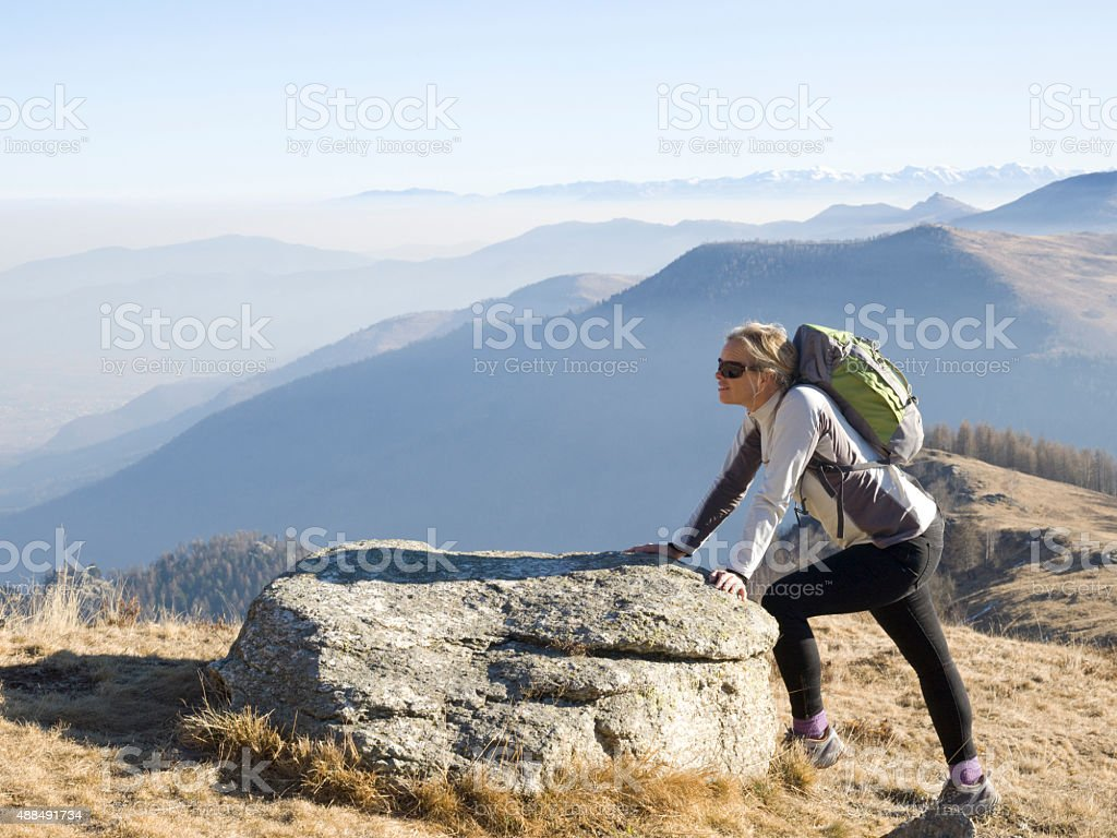 Hiker pauses to stretch by rock above mountains stock photo