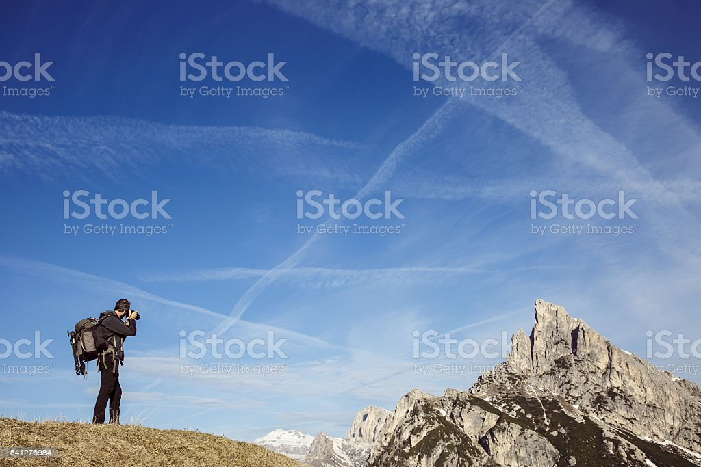 Hiker photographer taking photos on a mountain top stock photo
