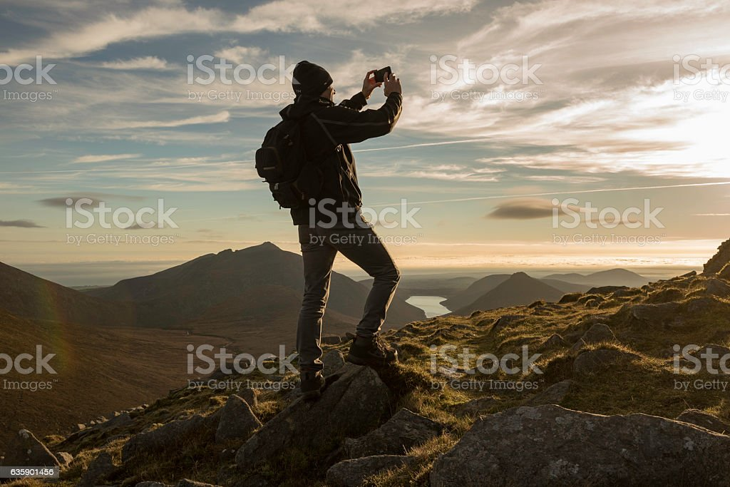 Hiker photographing Mourne Mountains, Northern Ireland stock photo