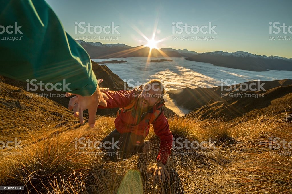 Hiker pulling out hand at mountain top asking for help stock photo