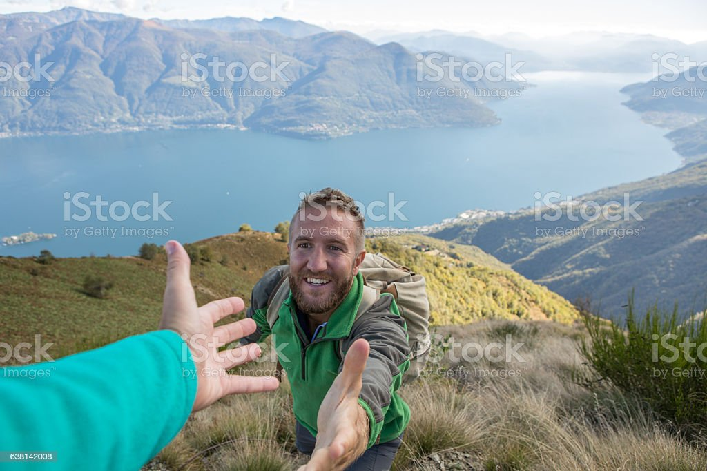 Hiker pulls out hand to get assistance from teammate stock photo