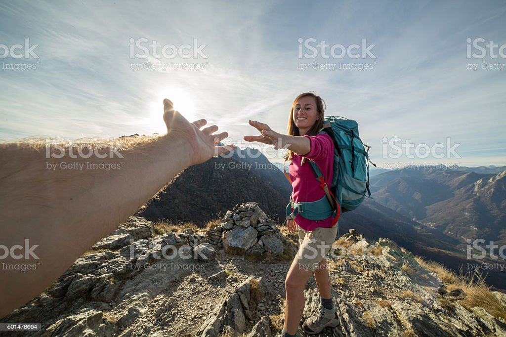 Hiker pulls out hand to reach teammate stock photo