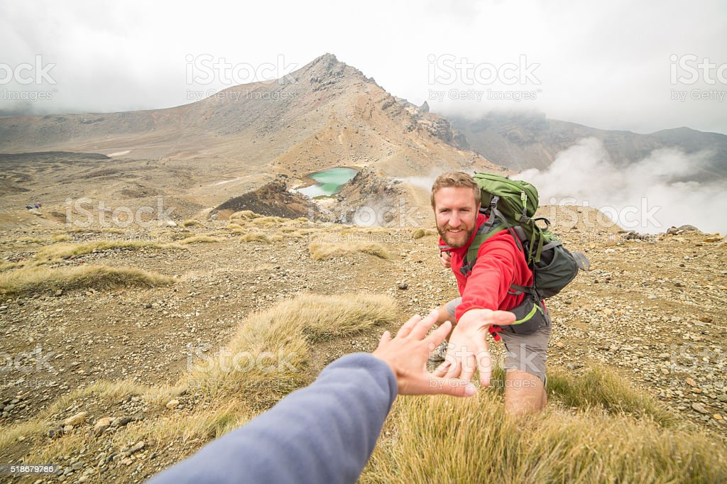 Hiker pulls out hand to reach teammate-New Zealand stock photo