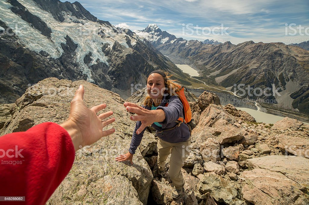 Hiker pulls out his hand to get assistance from teammate stock photo