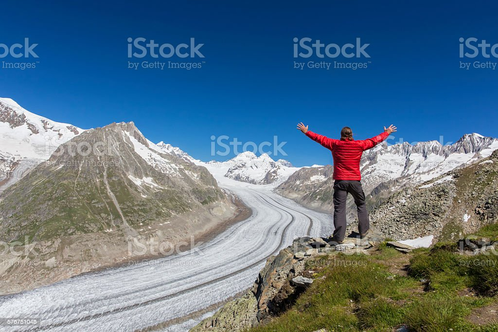 Hiker raising his Hands in front of Aletschgletscher stock photo