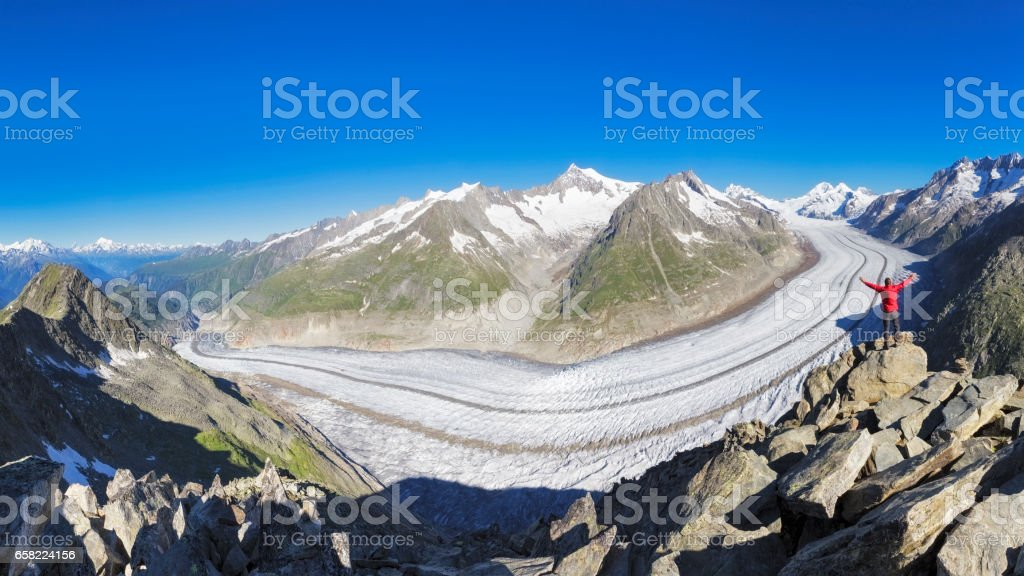 Hiker raising his Hands in front of Aletschgletscher stock photo