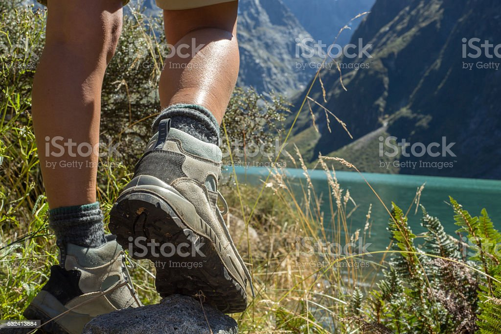 Hiker reaches mountain lake, close up on hiking boots stock photo