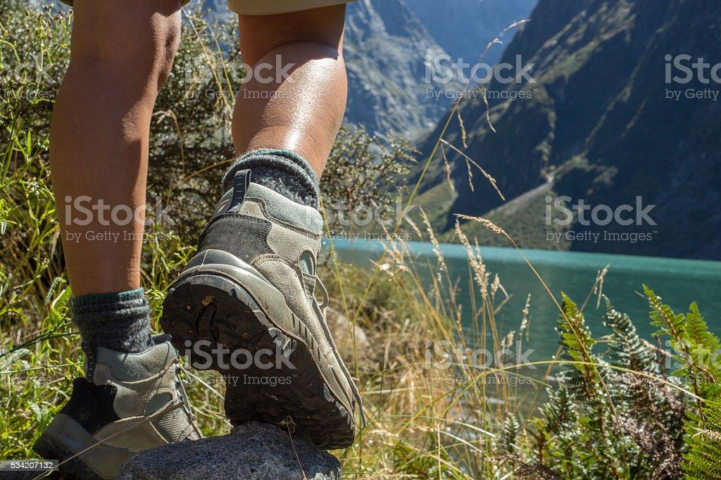 Hiker reaches mountain lake, close up on hiking shoes stock photo