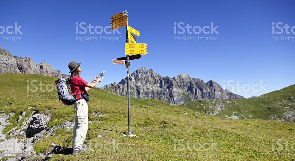Hiker Reading Map and Sings in the Swiss Mountains royalty-free stock photo