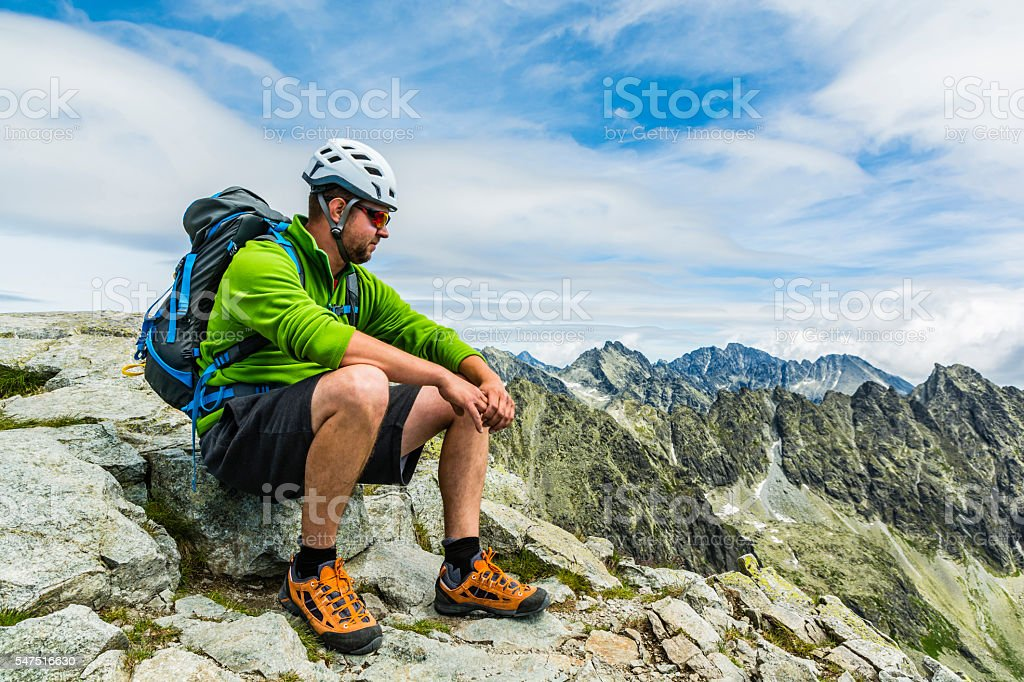 Hiker resting in mountains. stock photo