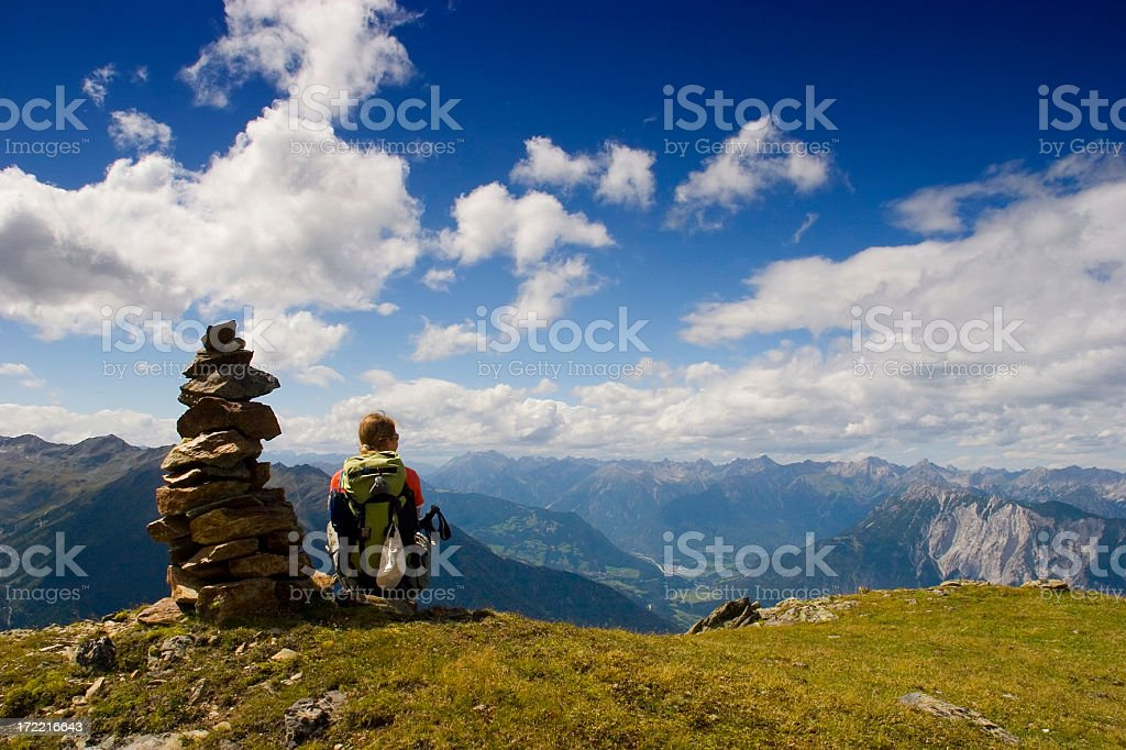 A hiker resting on the side of a mountain to see the view royalty-free stock photo