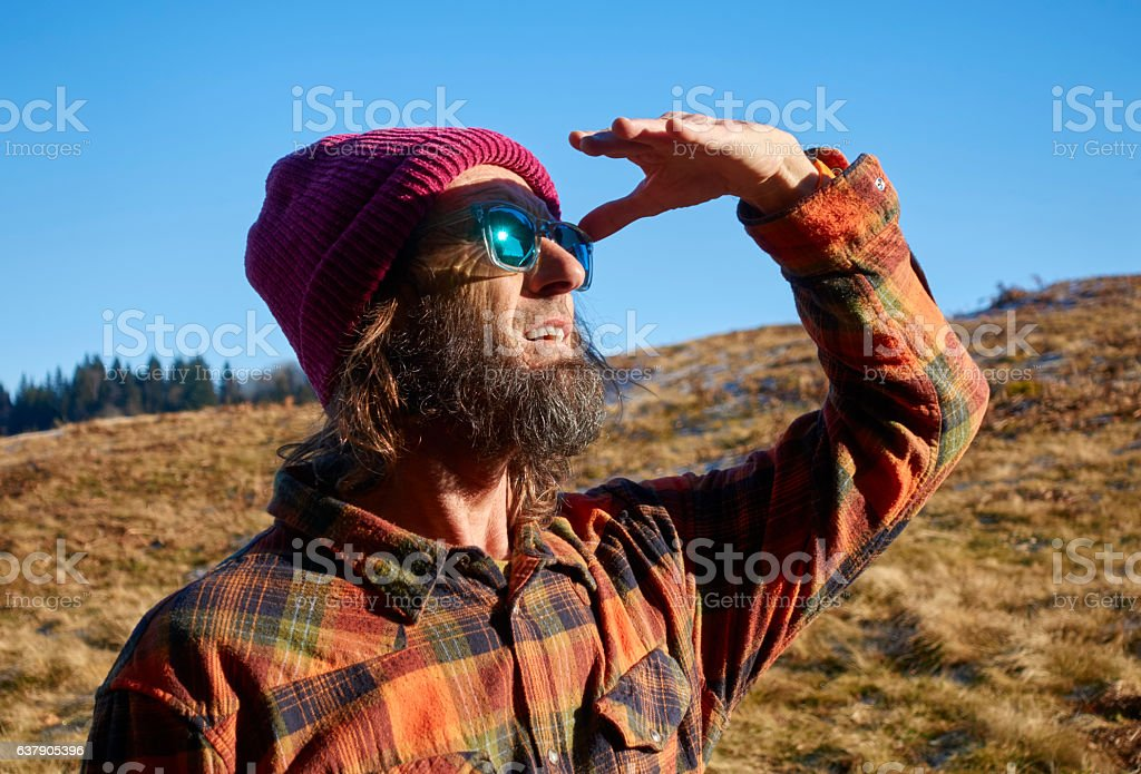Hiker Scanning the Horizon while Walking in the Swiss Mountains stock photo