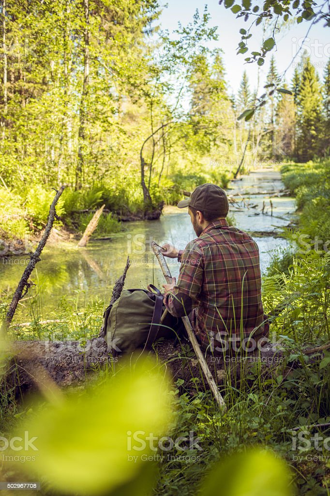 Hiker Sharpening a Hiking Pole Nearby Forest River stock photo