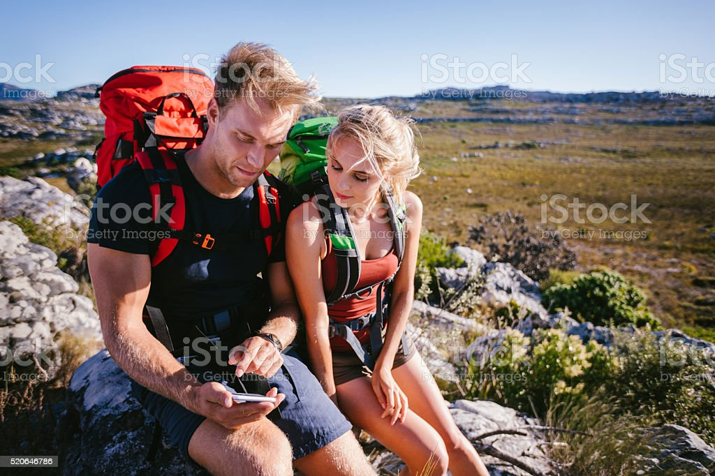 Hiker showing girl friend map on smartphone during outdoor activ stock photo
