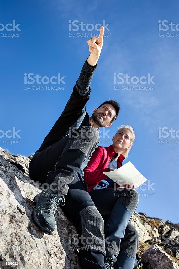 Hiker shows the way in the middle of the mountain stock photo