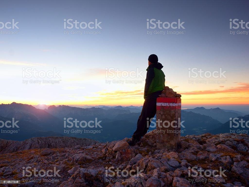 Hiker sit on border stone. Alps mountain. Daybreak above valley stock photo