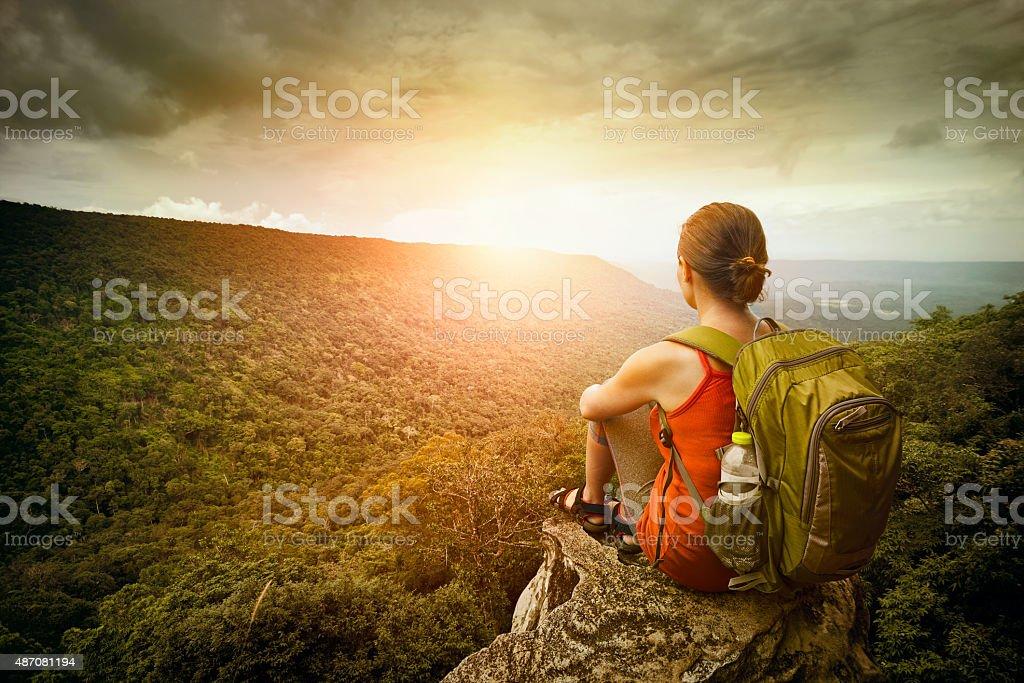 hiker sits on edge of the cliff and enjoying sunrise stock photo