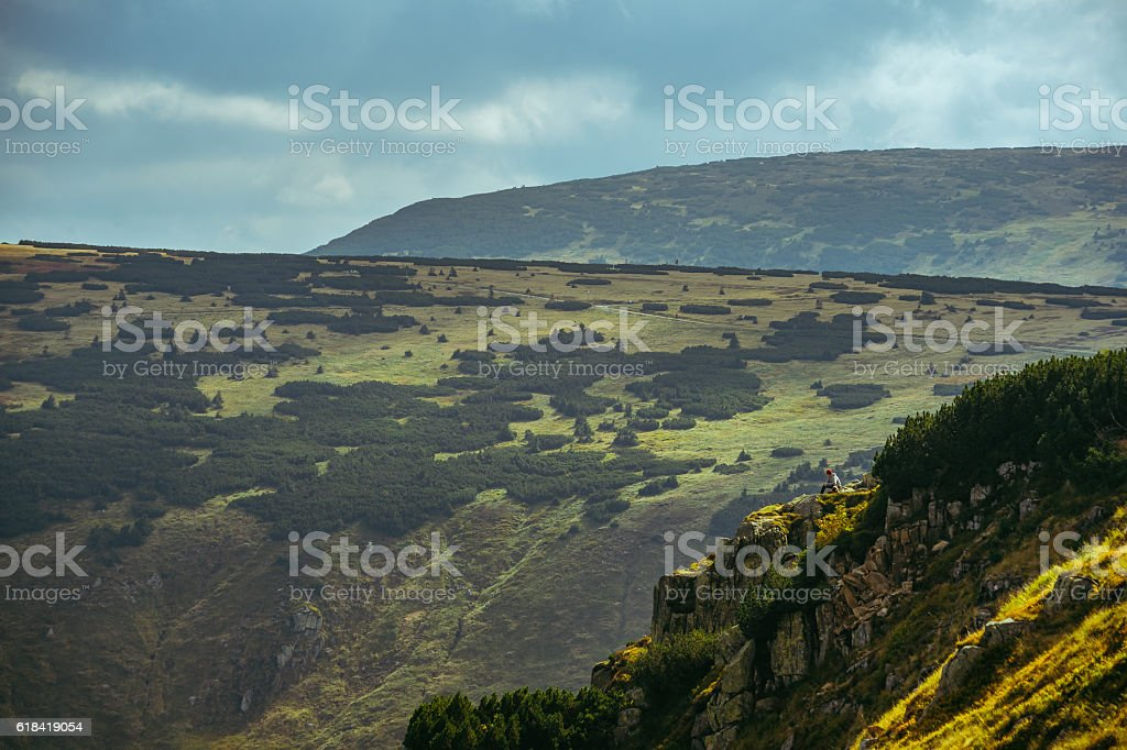 Hiker sitting next to a cliff in a giant mountain stock photo