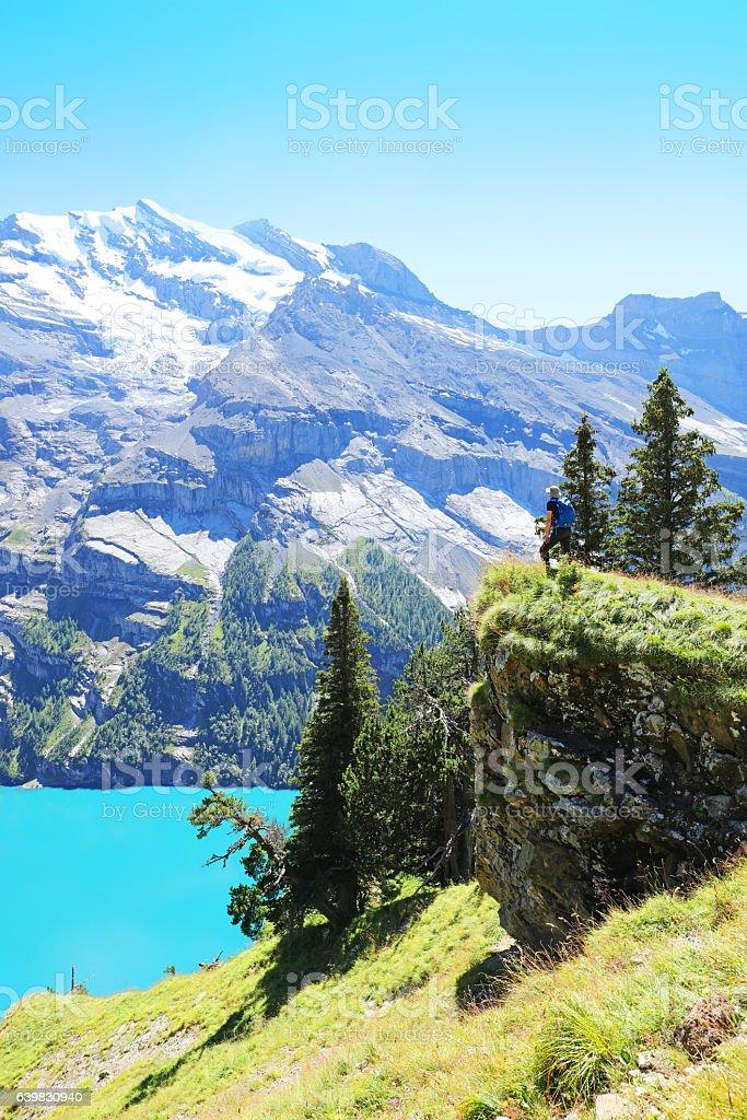 Hiker Standing at Oeschinen Lake Heuberg Lookout in Switzerland stock photo