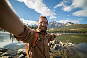 Hiker standing by the lakeshore takes selfie portrait in nature