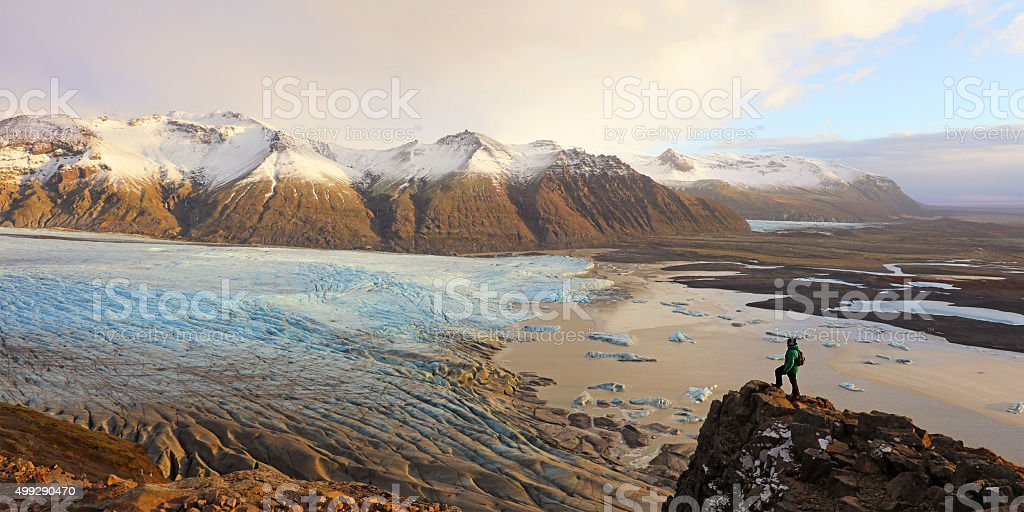 Hiker Standing on a Cliff Overlooking Skaftafell Glacier in Iceland stock photo
