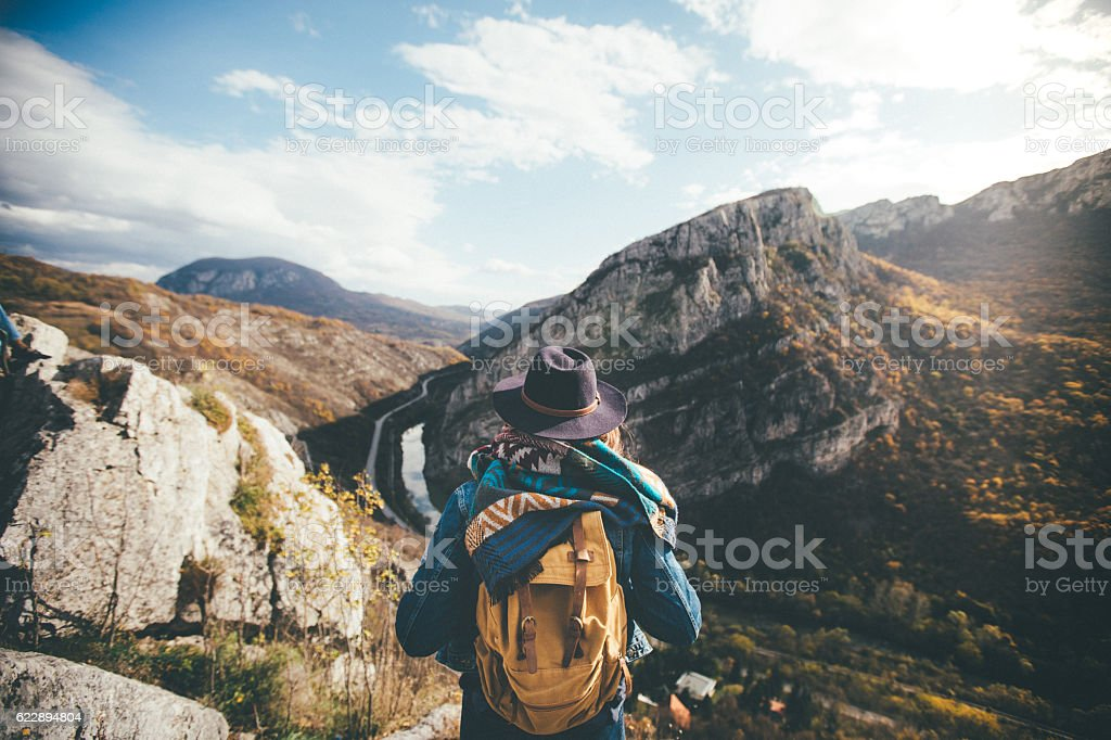 Hiker standing on edge of the cliff and enjoying sunlight stock photo