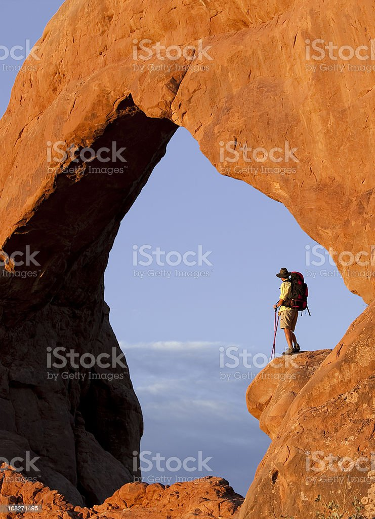 Hiker Standing On High Rocky Ledge In Arches National Park royalty-free stock photo
