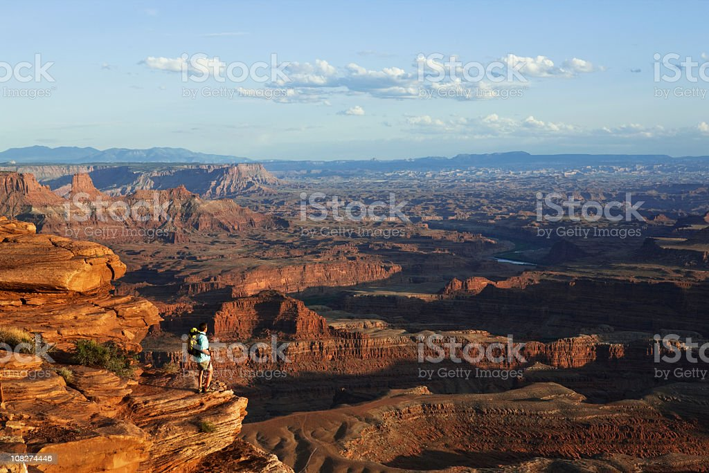 Hiker Standing On Rocky Ledge Looking At View In Utah stock photo