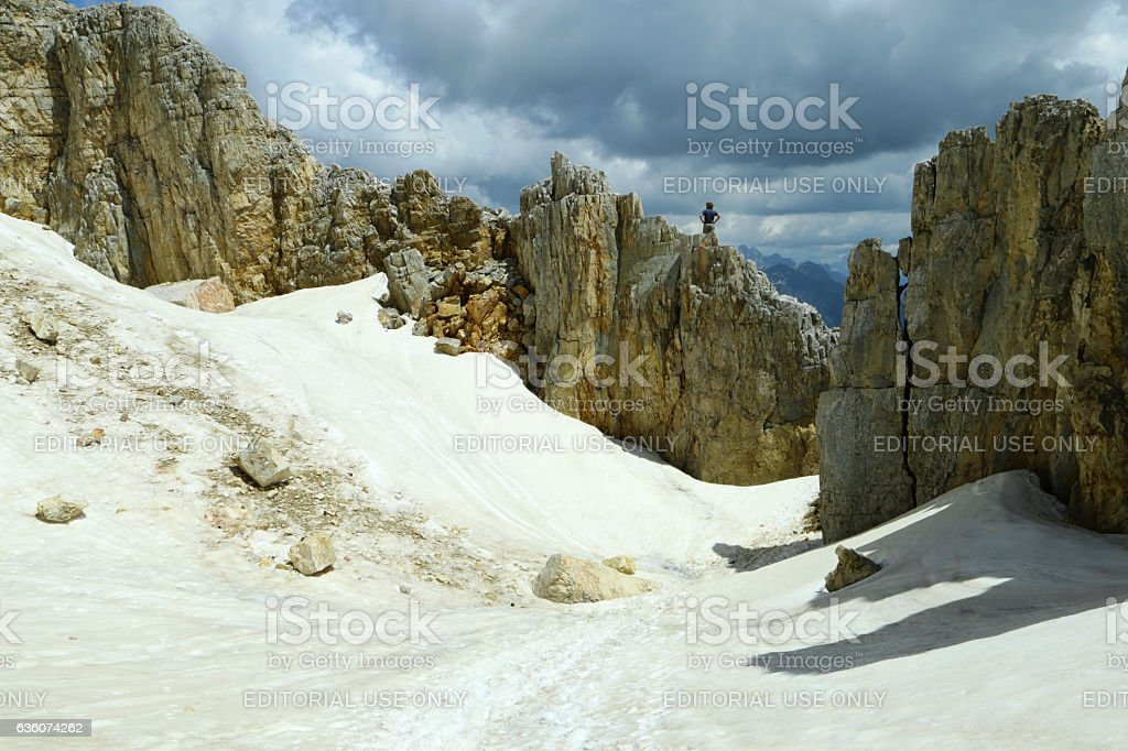Hiker standing on the rock, and snow in the soil stock photo