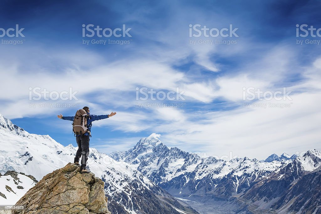 A hiker standing on top of a snow mountain rock  stock photo