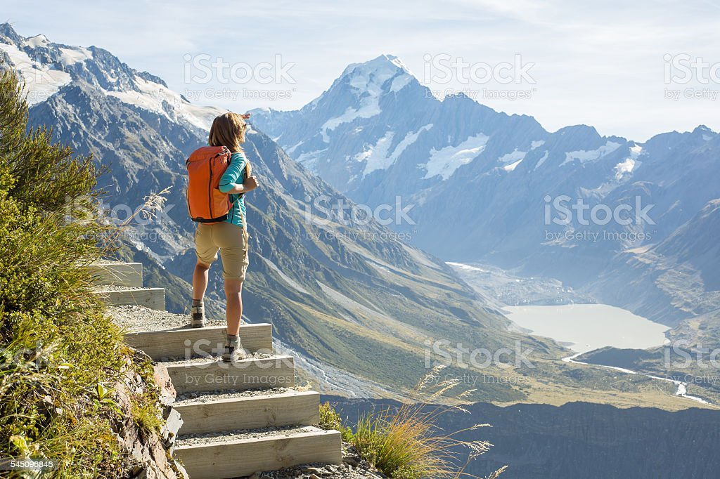 Hiker stands on a mountain top and admires view stock photo