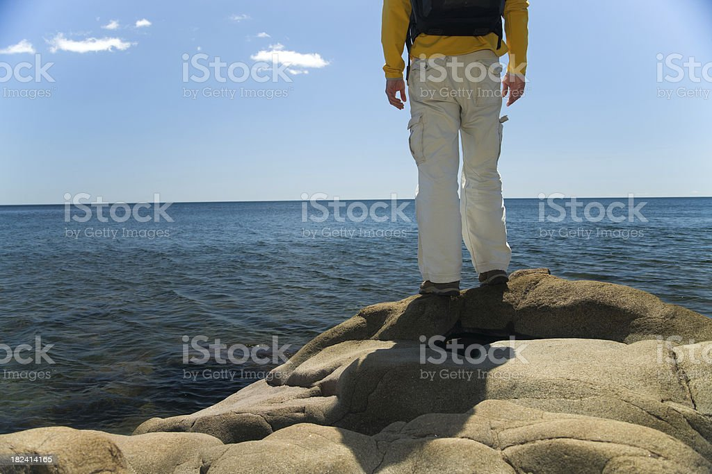 Hiker stands on Lake Superiors rocky shoreline. royalty-free stock photo