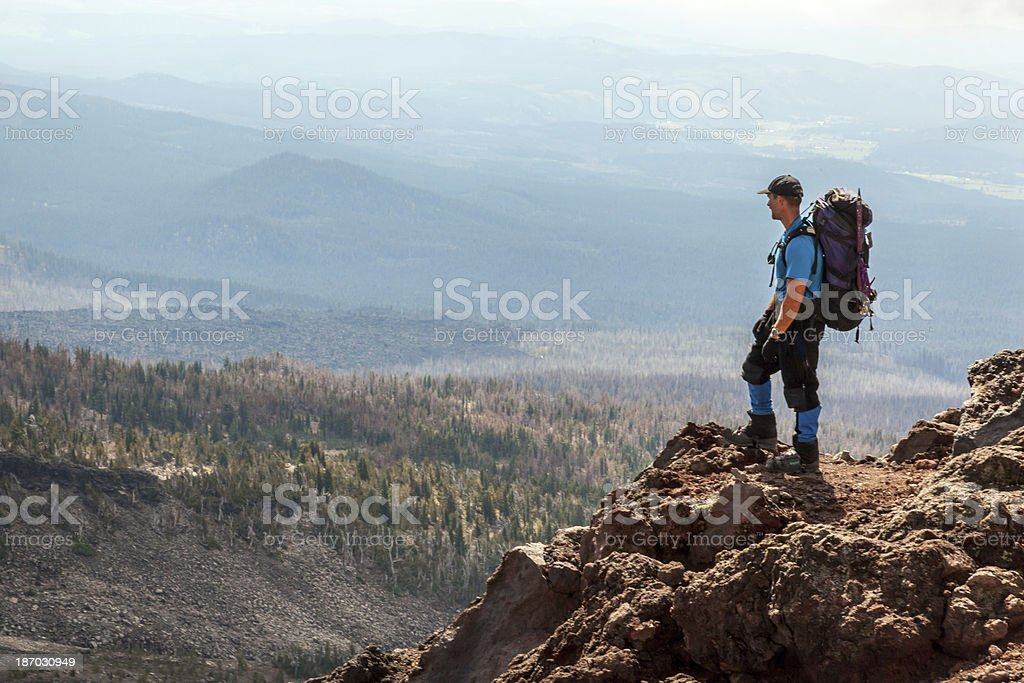 Hiker stands on side of Mount Adams in Washington stock photo