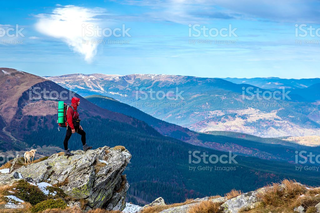 Hiker staying on rocky Cliff observing Mountains Panoramic View stock photo