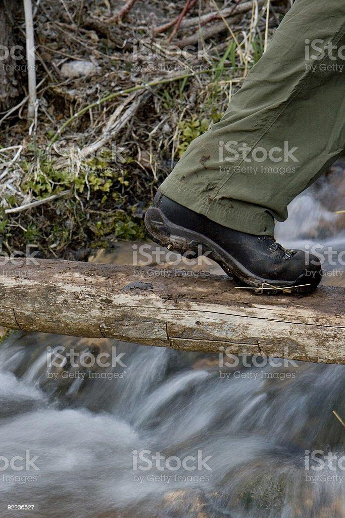 Hiker stepping on log foot bridge royalty-free stock photo