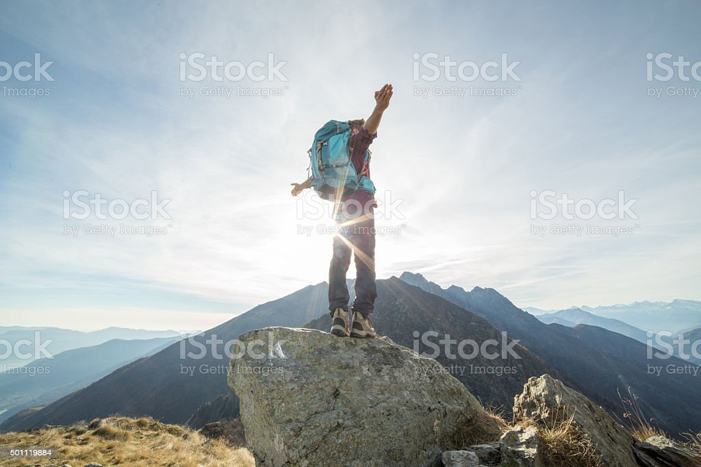 Hiker stretches arms to sunset, mountains stock photo