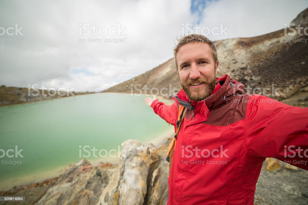 Hiker takes a selfie portrait by an Emerald lake stock photo