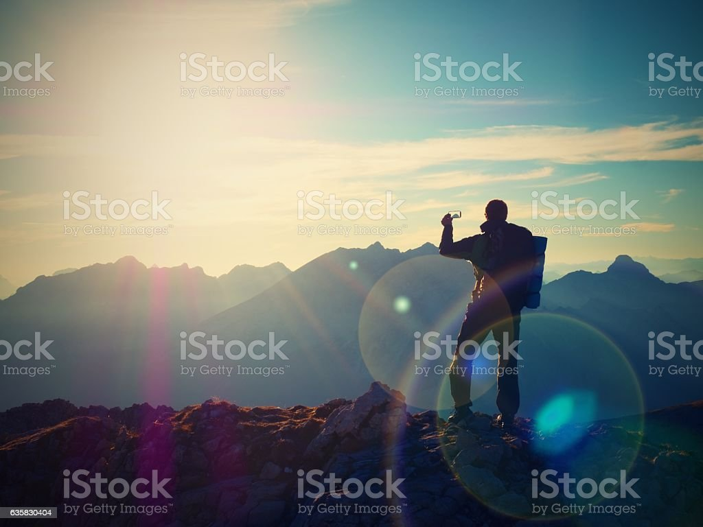 Hiker takes selfie photo. Man with backpack  walk on mountain stock photo