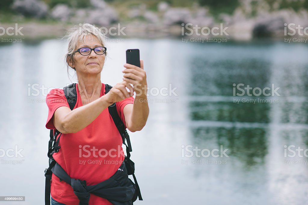 Hiker taking a selfie in the mountains stock photo