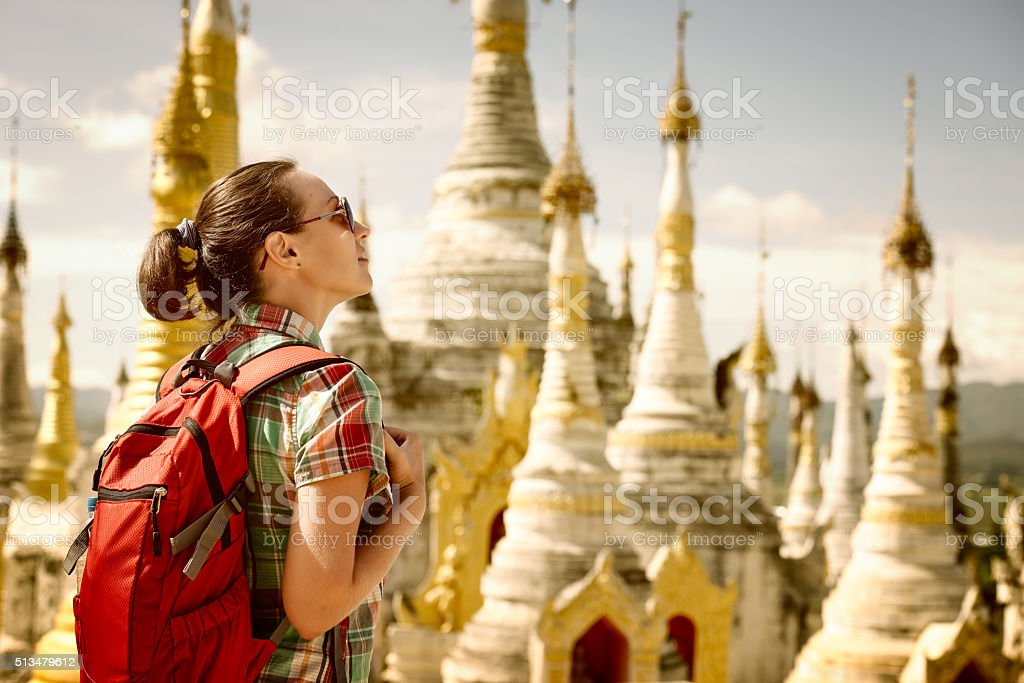 Hiker traveling  with backpack and looks at Buddhist stupas. stock photo