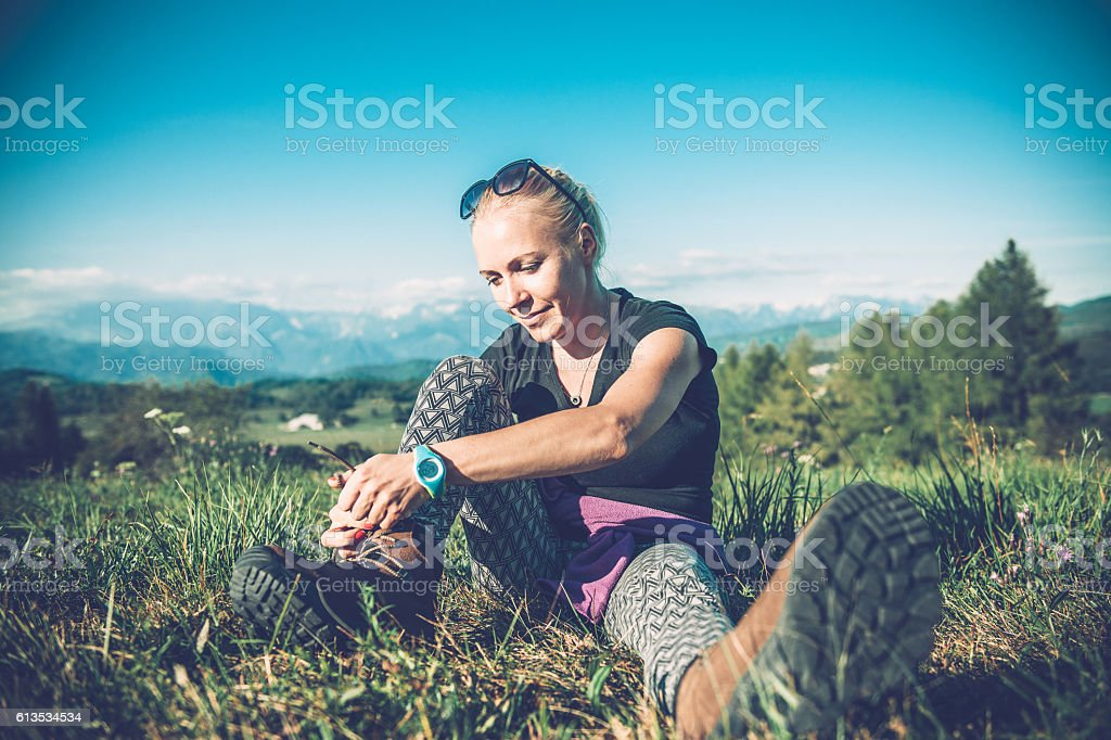 Hiker tying her shoe in the mountains, Europe stock photo