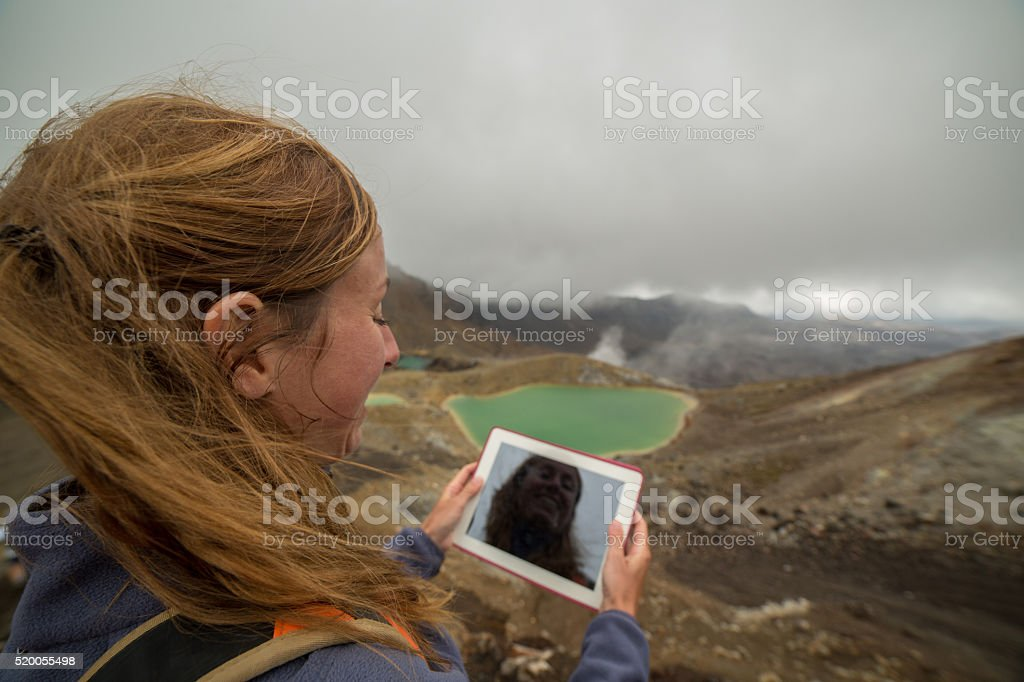 Hiker uses a digital tablet by the mountain lake stock photo