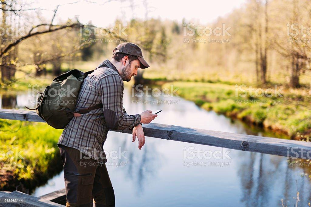 Hiker Using Smartphone in Nature stock photo