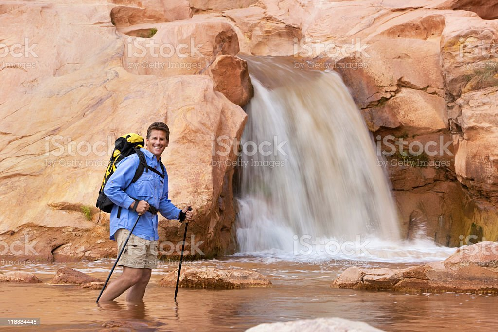 Hiker Wading In Water At Bottom Of Waterfall royalty-free stock photo
