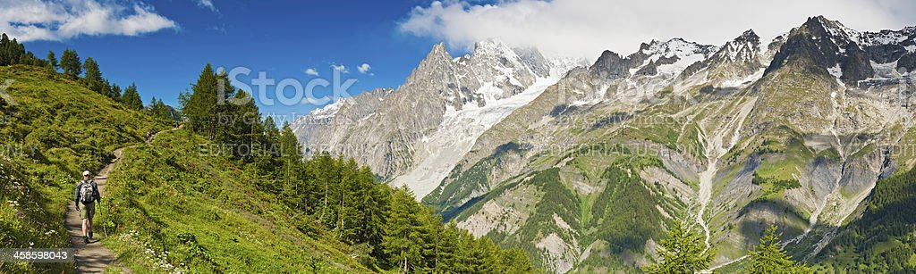 Hiker walking idyllic Alpine meadow trail mountain peaks panorama royalty-free stock photo