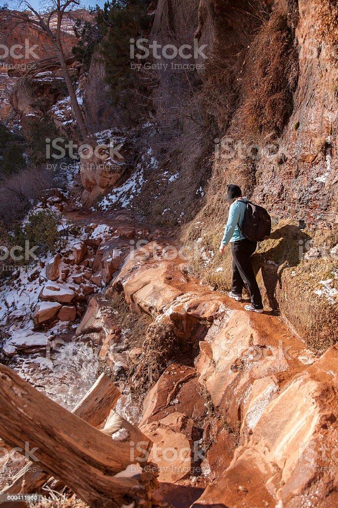 Hiker walking narrow footpath on edge of dangerous cliff stock photo