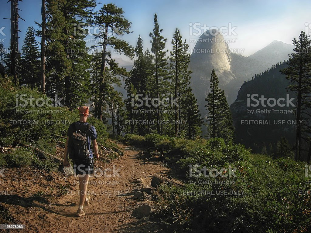Hiker Walking on Trail with Half Dome in the Background stock photo