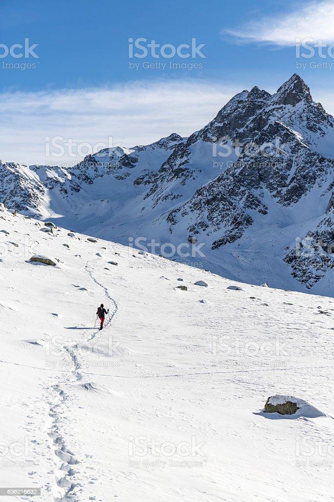 Hiker walks on snowy mountain stock photo