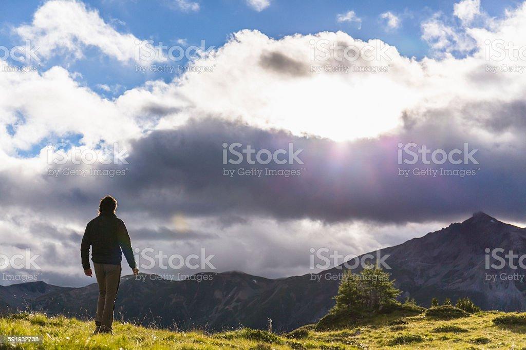 Hiker walks on the mountain path stock photo